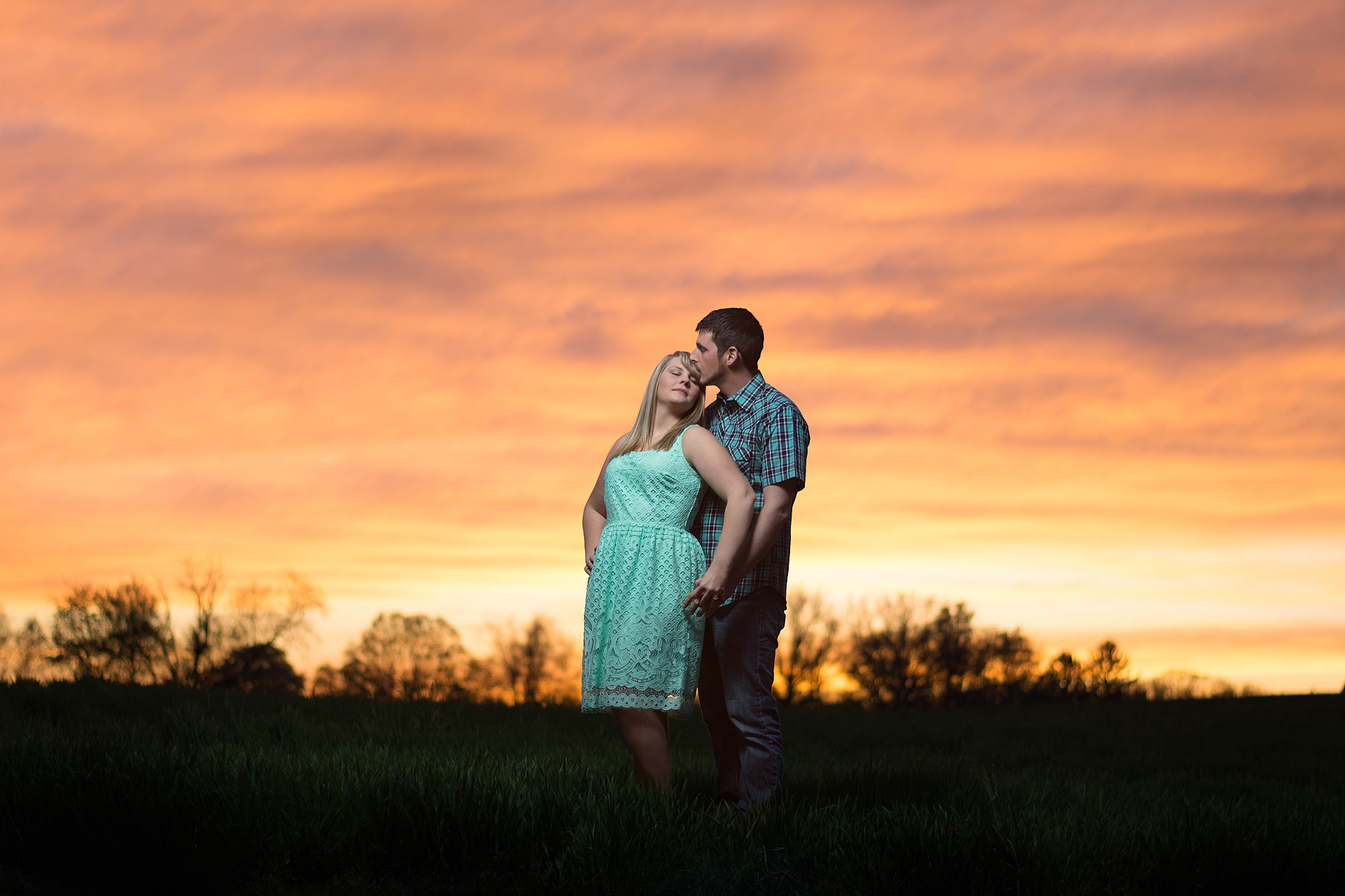 Engaged Couple Posing in Ohio Field in Front of Gorgeous Sunset | Kropp Photography