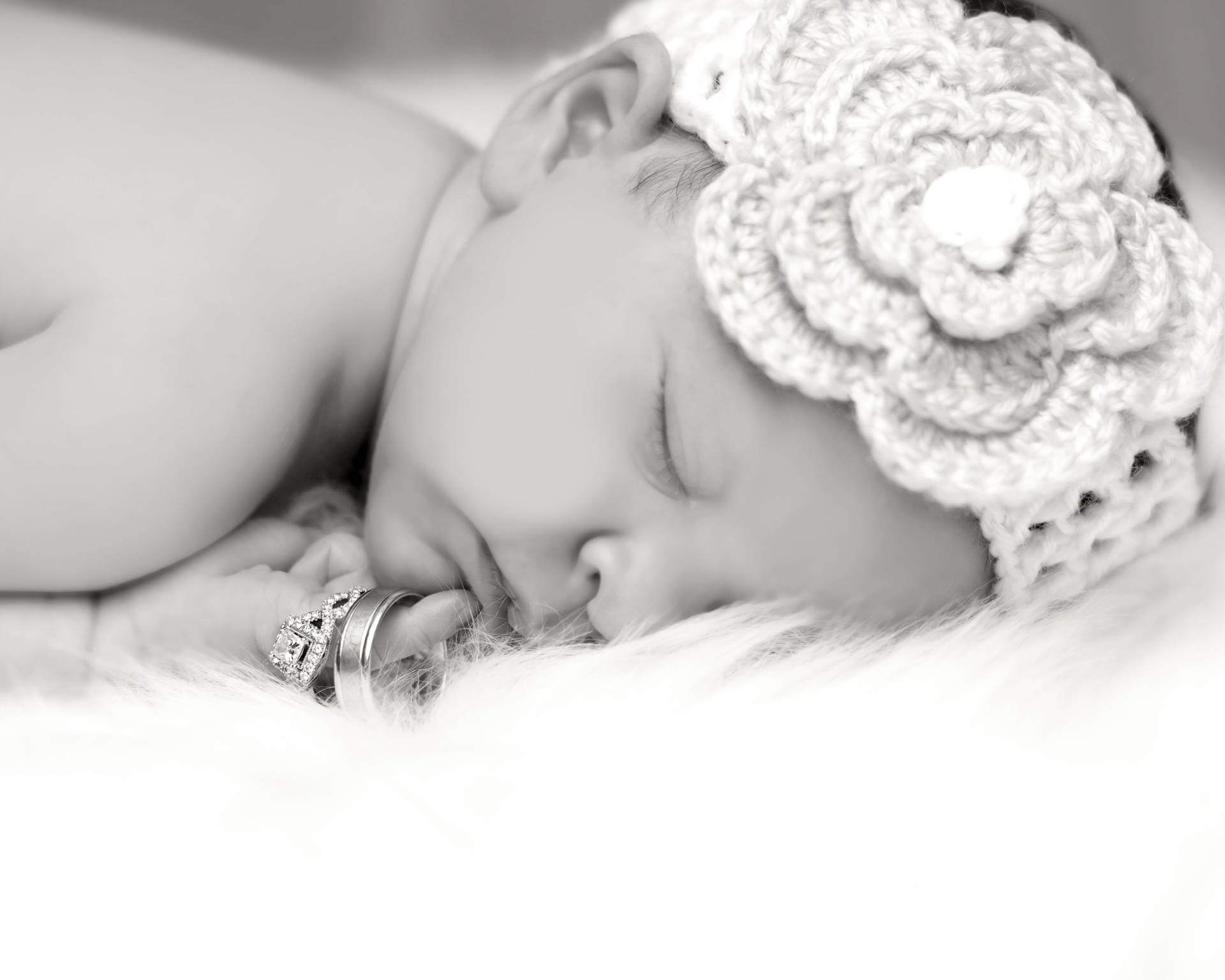Black and white image of sleeping newborn baby with a flower in her hair and holding her parents wedding rings