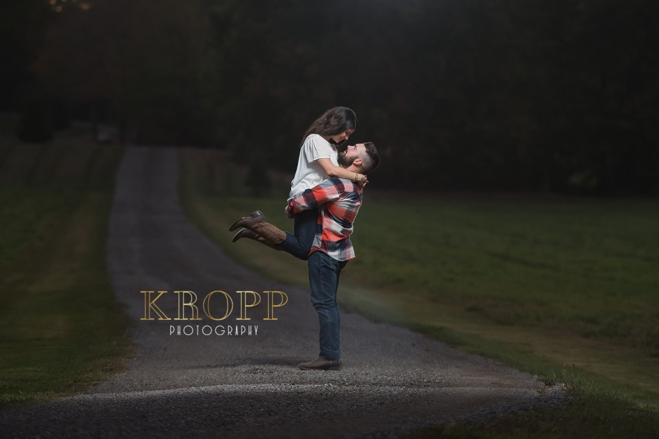 Engaged couple embracing on long driveway