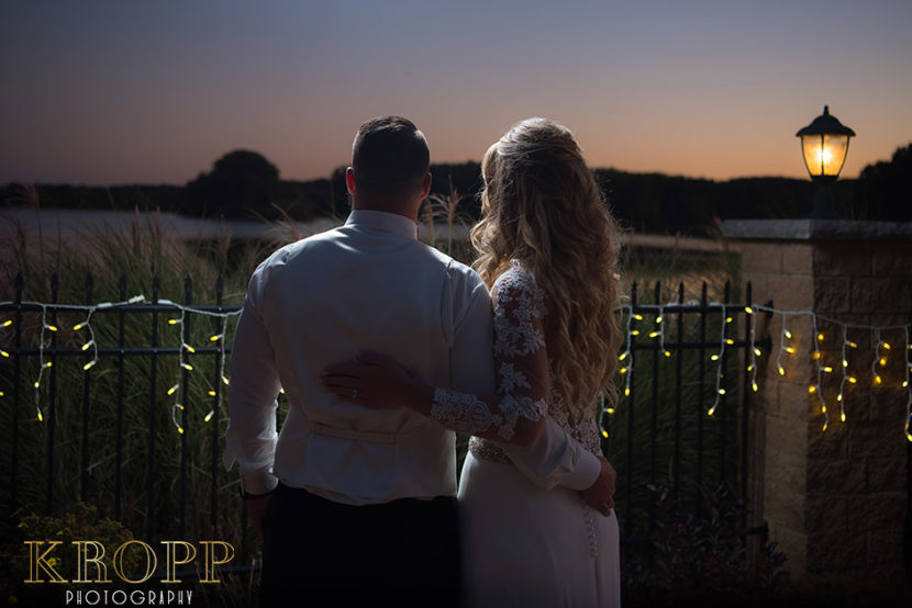 Husband and wife gazing out over lake during wedding reception at Avion Banquet Center