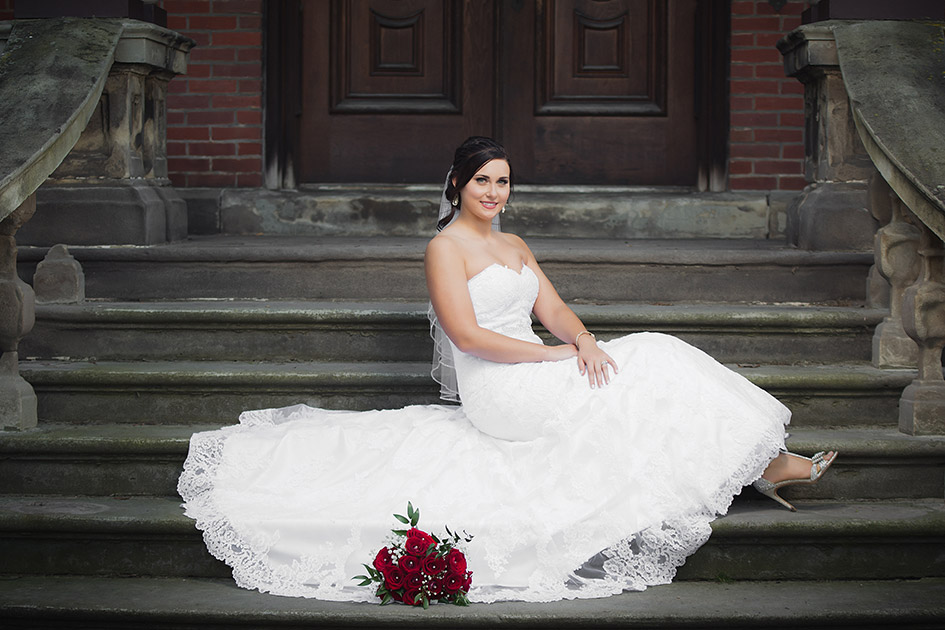 beautiful bride sitting on stairs in her wedding dress with her red rose wedding bouquet and her wedding shoes showing | Kropp Photography