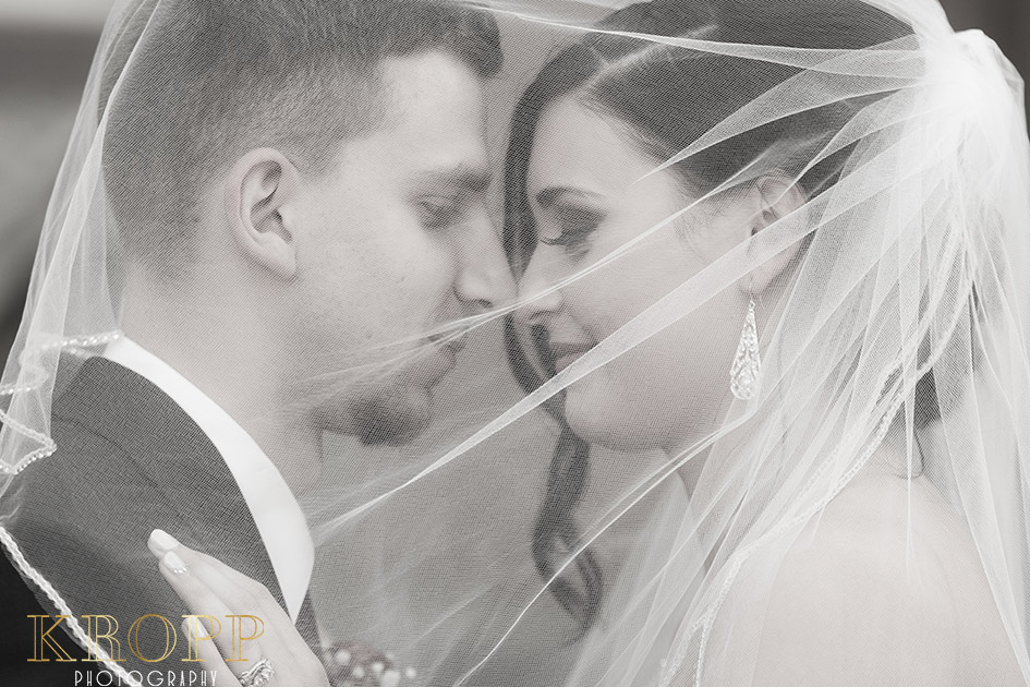 Bride and groom lovingly close under bridal veil in black and white