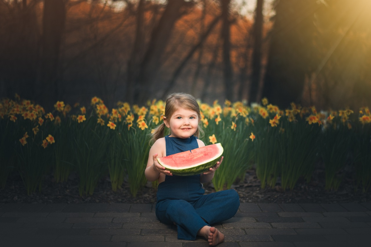 Pretty Little Girl Eating Watermelon in Overalls while sitting in front of yellow daffodils at Fellows Riverside Gardens in Mill Creek Park | Kropp Photography