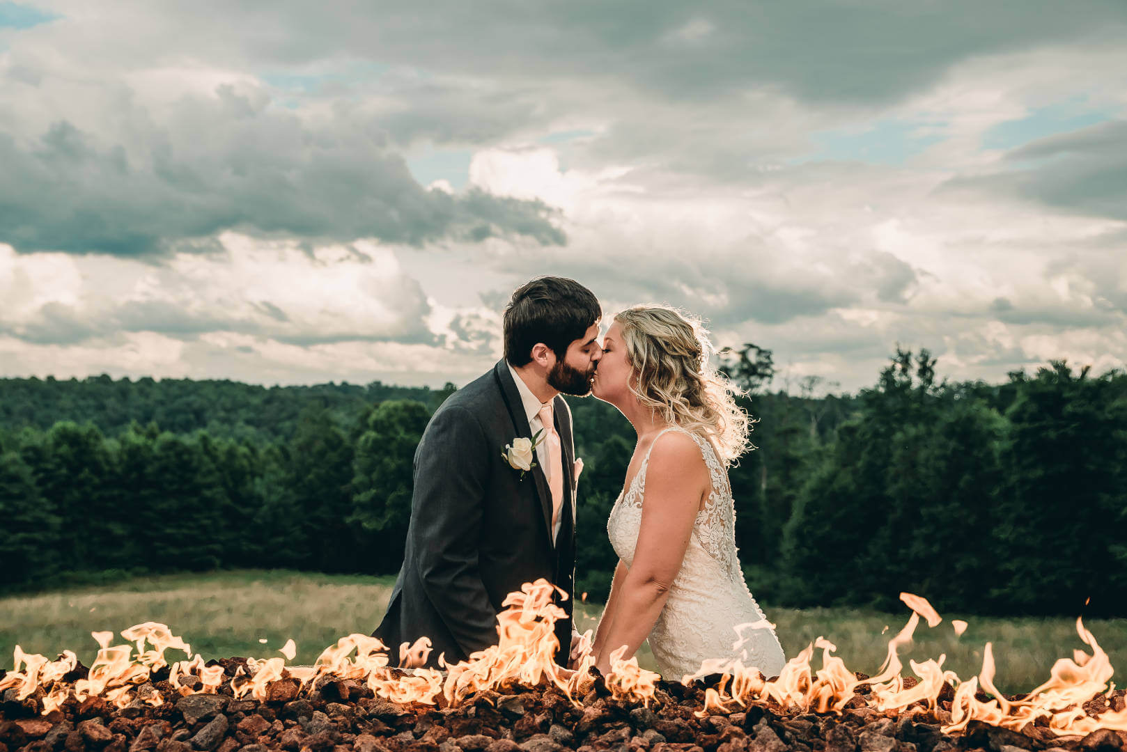 Bride and Groom Kissing in Front of Fire at Bella Amore on Enchanted Acres | by Kropp Photography | Cleveland Wedding Photographers