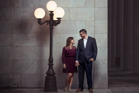 Lovely Young Couple Holding Hands Near a Streetlight In Front of a Marble Wall at McKinley Memorial Library | Kropp Photographers - Youngstown Wedding Photographers
