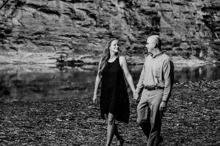 Lara + Karl | Black and White of Lovers Walking Along Riverbed Holding Hands | Rocky River Reservation Engagement Session