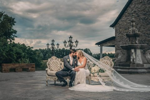 bride and groom sitting on elegant white leather couch with brides veil flowing behind her at bella amore on enchanted acres in dennison ohio