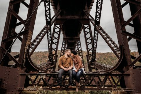 Engagement photo of couple sitting on Kinzua Bridge in Pennsylvania | by Kropp Photography | Cleveland Wedding Photographers