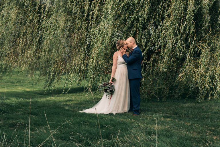 Bride and groom kissing in front of beautiful weeping willow tree near Inn Walden in Aurora Ohio | by Kropp Photography | Cleveland Wedding Photographers