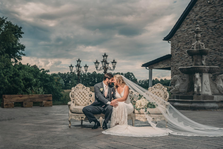 Newlyweds on white couch in front of fountain at Bella Amoré on Enchanted Acres | Kropp Photography