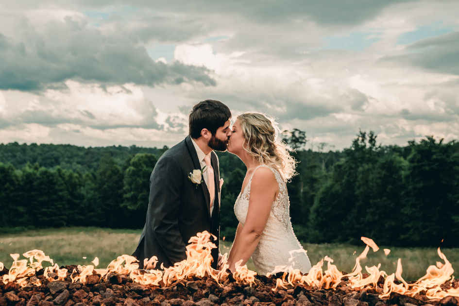 Bride and Groom kissing in front of flame of fire at Bella Amore on Enchanted Acres | Kropp Photography