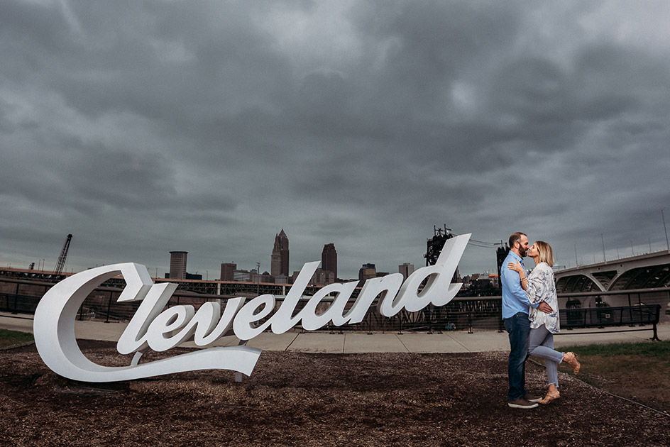 Cleveland Script Sign and our loving couple sharing a kiss and an embrace with the Cleveland skyline in the background | Kropp Photography