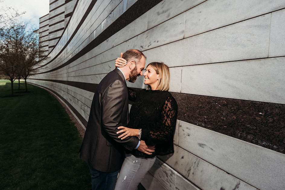 Loving engaged couple with their faces pulled close together against the exterior wall of the Cleveland Museum of Art in Cleveland Ohio | Kropp Photography