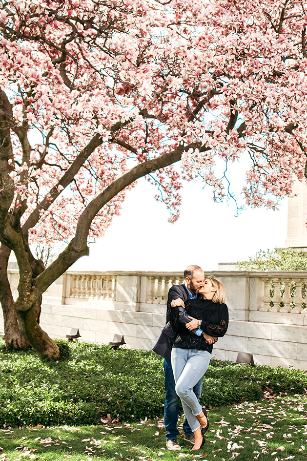 Couple stealing a kiss under the blossoms of a cherry tree at the Cleveland Museum of Art in Cleveland Ohio | Kropp Photography