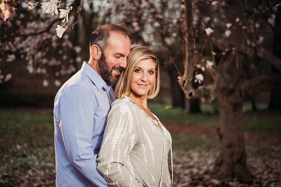 Engaged couple warmly embracing under blossoming cherry trees