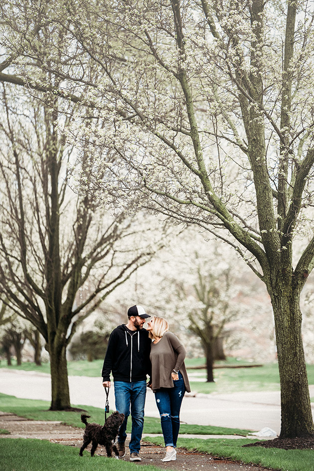 Engaged couple walking down tree lined street walking dog and stopping to kiss each other | Kropp Photography