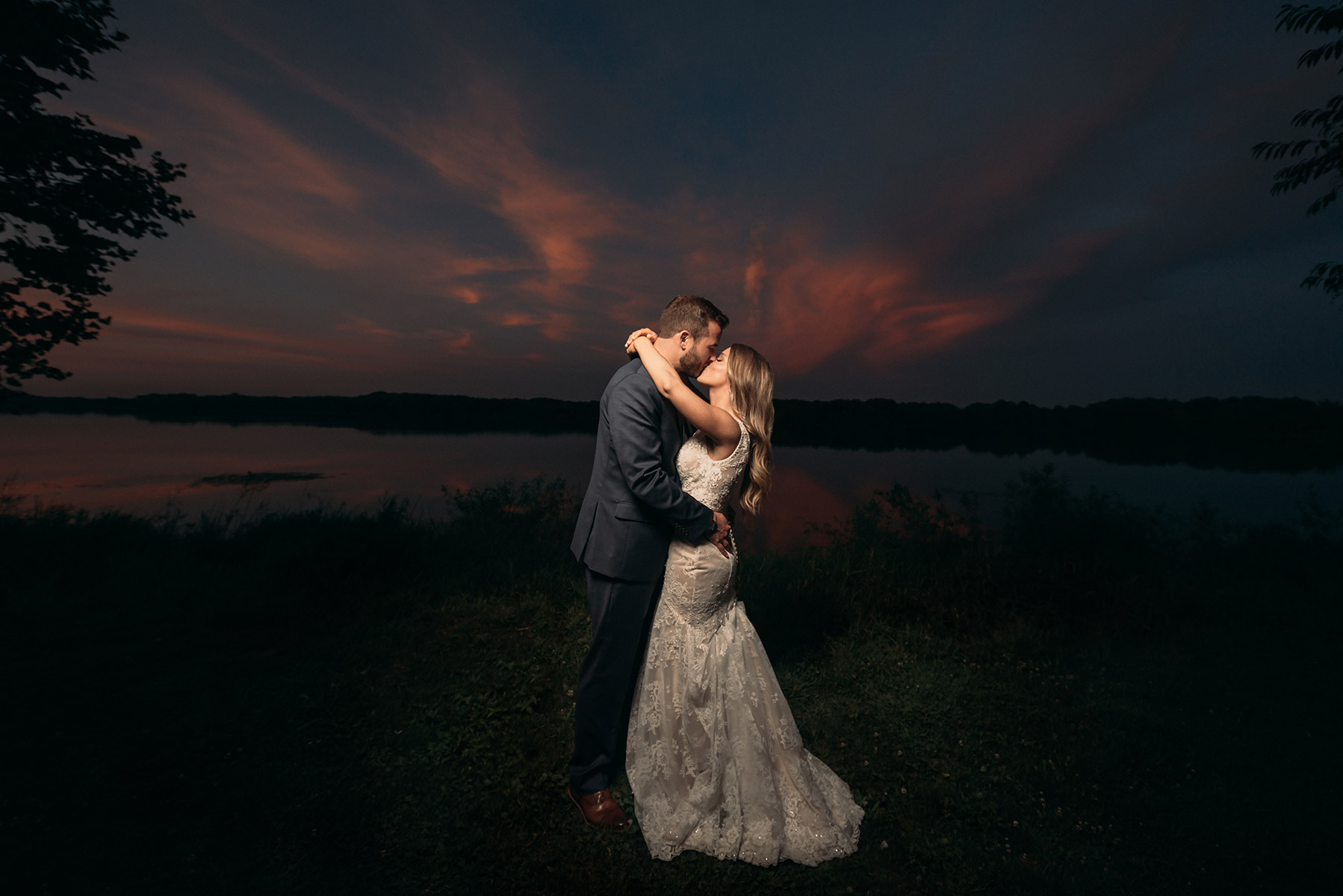 beautiful bride and groom embrace during sunset in front of pine lake at the vineyards at pine lake