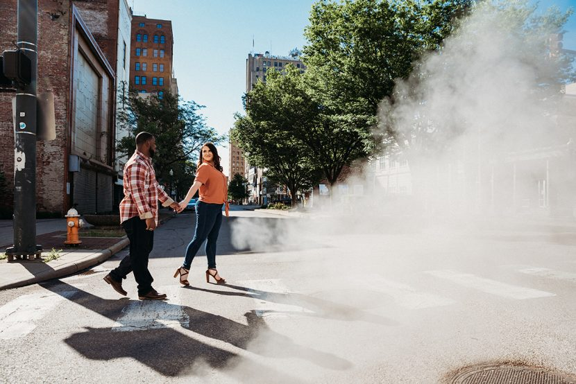 loving couple holding hands walking across the street in downtown youngstown | by Kropp Photography