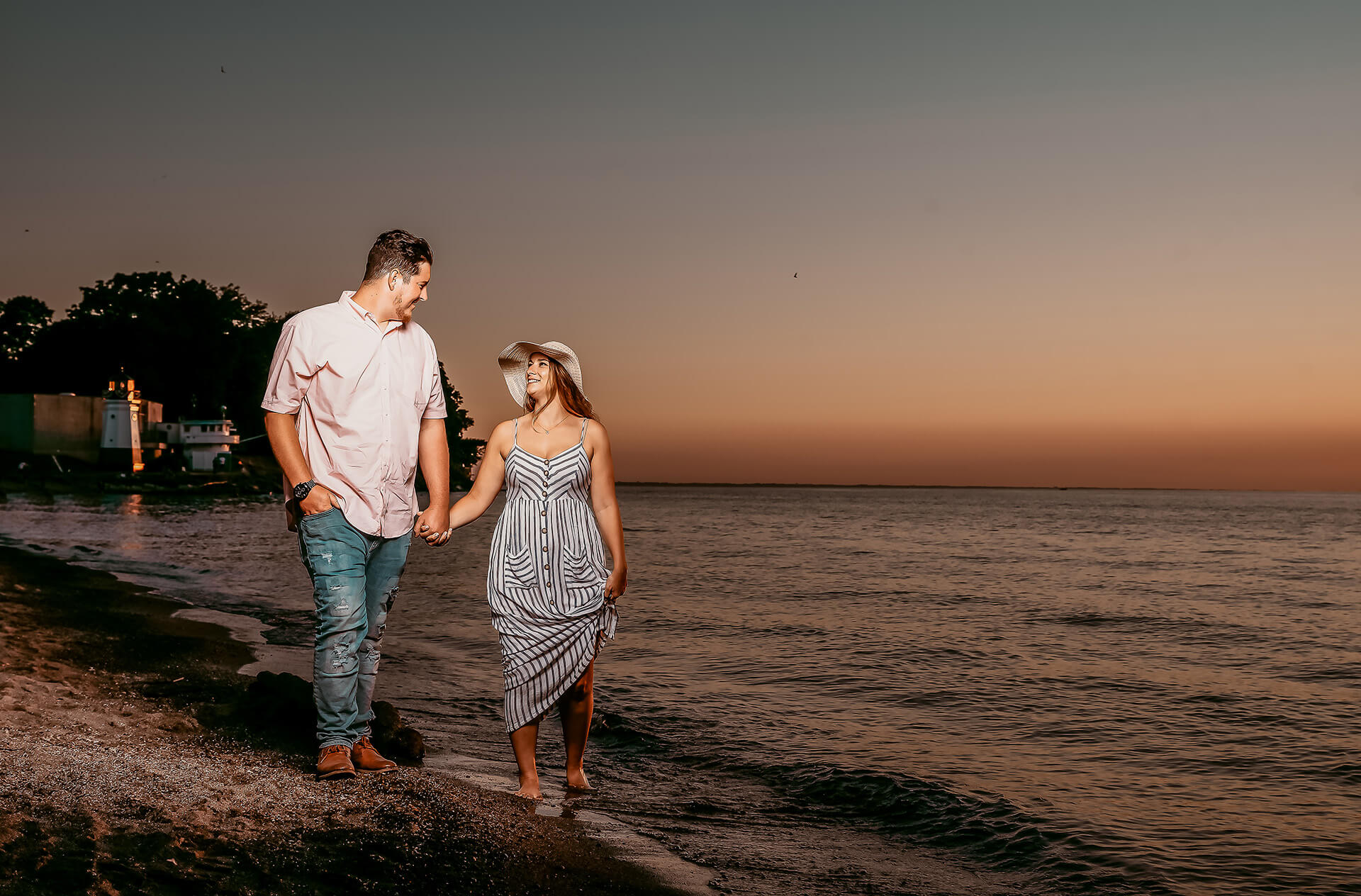 Engaged young couple walking along the beach in Vermilion on the Lake with the Vermilion Lighthouse in the background at sunset
