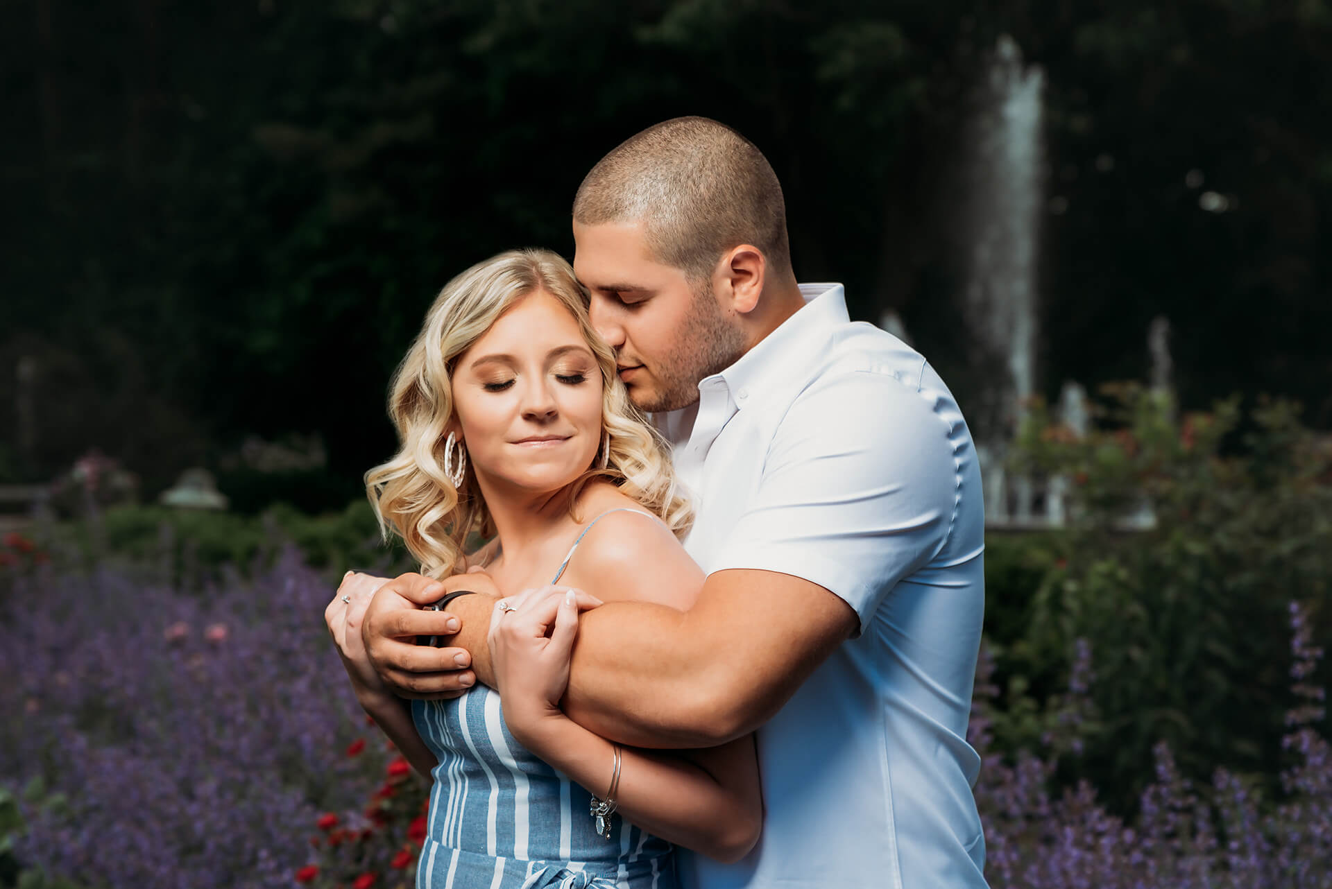 Mill Creek Park engagement photos with attractive young couple embracing each other with flowers and a water fountain in the background