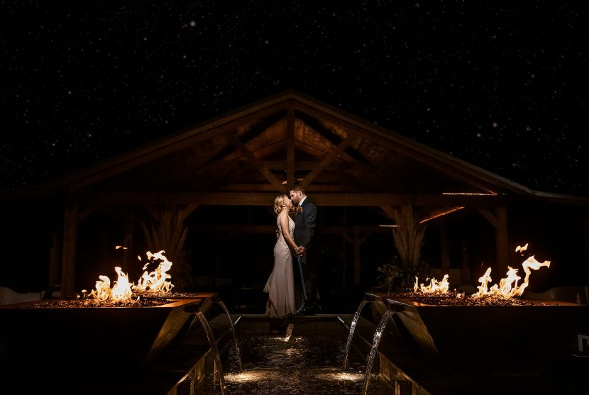 Bride and Groom standing in front of flames and waterfalls at Sapphire Creek Winery wedding | by Kropp Photography