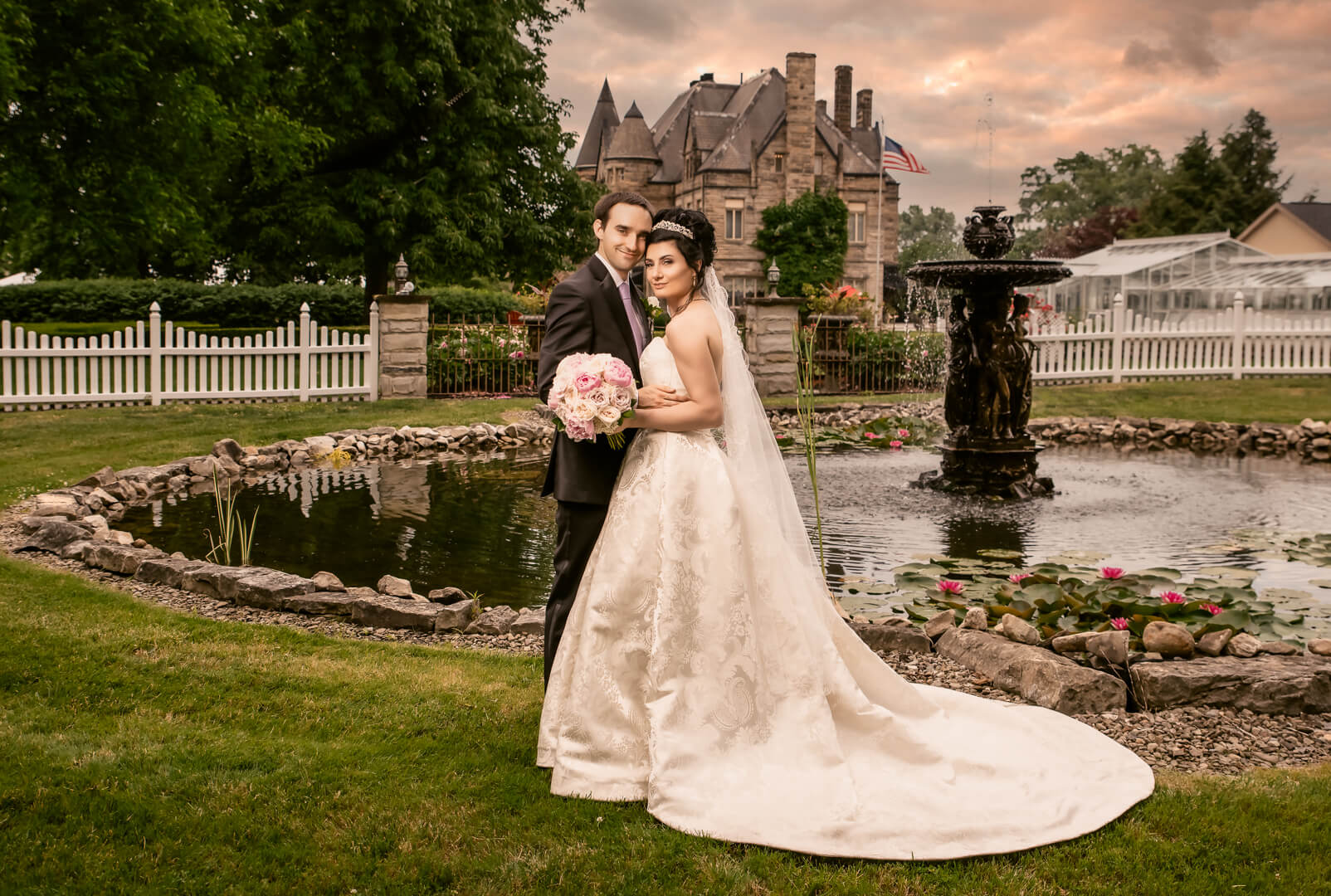 Bride and groom standing in front of a fountain with Buhl Mansion in the background   by Kropp Photography