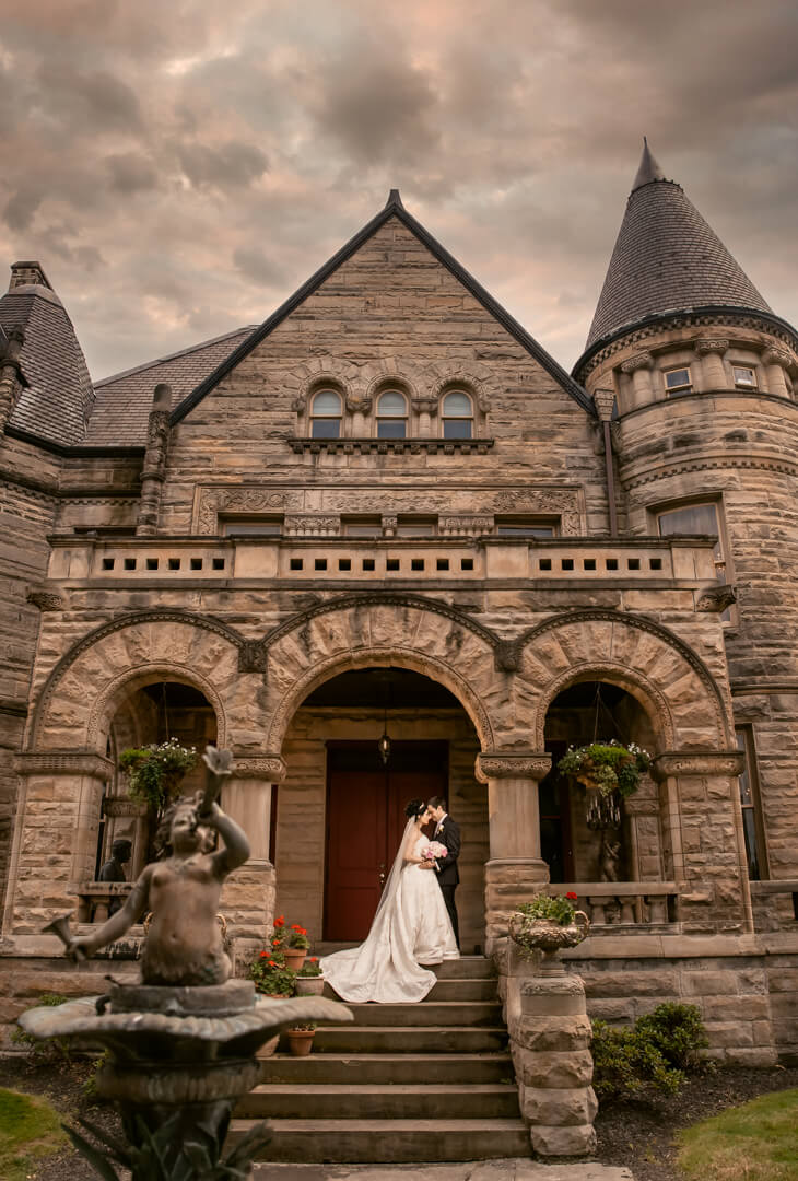 New Bride and Groom standing underneath the archway at the front entrance of Buhl Mansion | by Kropp Photography