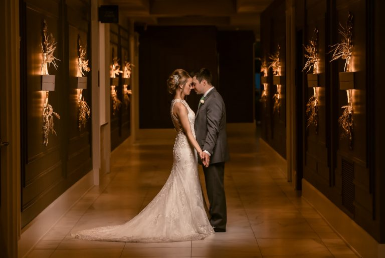 New Bride and Groom standing in the hallway of Waypoint 4180 with beautiful golden wall sconces behind them